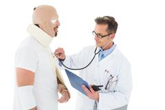 Doctor auscultating patient tied up in bandage with stethoscope - stock photo