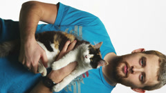 A cat is being held by a man with a blank stare on his face Stock Footage