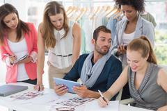 Fashion designers discussing designs - stock photo