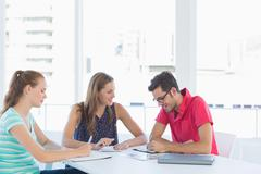 Three casual artists working on designs - stock photo