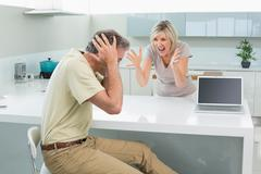Stock Photo of Man covering his ears as woman argue in kitchen