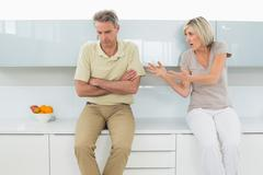 Man with arms crossed as woman argue in kitchen - stock photo