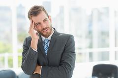 Young businessman with severe headache in office - stock photo