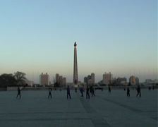 People playing under the Juche Tower in Pyongyang Stock Footage