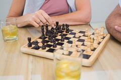 Mid section of a woman and man playing chess Stock Photos