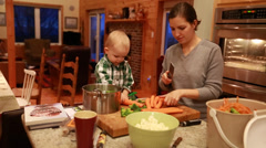 A toddler helping his mother cook dinner Stock Footage