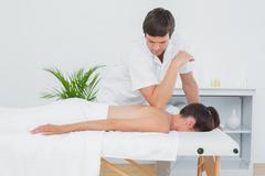 Male physiotherapist massaging woman's back Stock Photos