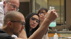 A college professor helps students understand a chemistry experiment - stock footage