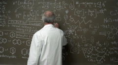 A professor poses his arms crossed in front of a chalkboard full of equations - stock footage