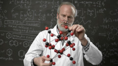 A professor stands in front of a blackboard of a model of a chemical molecule Stock Footage
