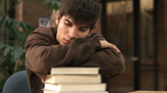 A tired college student rests his head on a pile of text books - stock footage