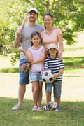 Family of four holding baseball bat and ball in park Stock Photos