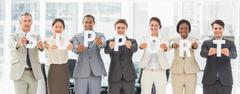 Diverse business team holding up letters spelling support Stock Photos