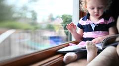 A cute little girl flips through her book - stock footage