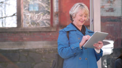 An older woman uses her tablet while waiting for the bus Stock Footage