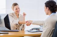 Stock Photo of Smartly dressed women shaking hands in business meeting