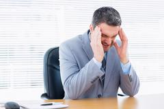 Businessman with severe headache at office desk Stock Photos