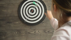 Little girl throwing darts at the target, focus on the target Stock Footage