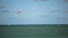 A person floats in a parasail behind a boat in the ocean Stock Footage