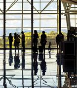 Silhouettes of unrecognizable traveling people at the airpor Stock Photos
