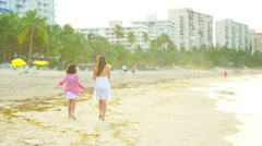 A young girl and her mother fly a kite in the water at the beach - stock footage