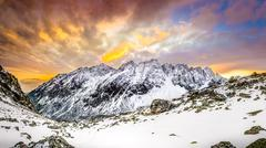 panoramic view of white winter mountains after colorful sunset - stock photo