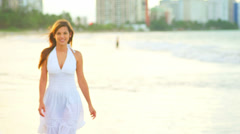 A young woman walks along the water's edge at the beach during sunset Stock Footage
