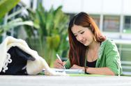 Stock Photo of beautiful young asian student is reading and writing