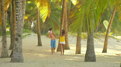 Two teenagers walk through some trees at the beach Stock Footage