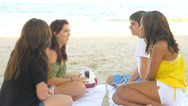 Stock Video Footage of Four teenagers sit on a blanket on the beach and talk in the sand