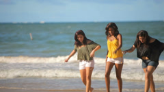 Three teenage friends walk out of the water and up the beach during the day Stock Footage