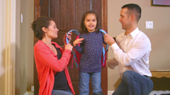 A cute little girl gets help with her backpack from both her mom and dad Arkistovideo