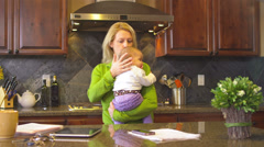A stressed out mom tries multitasking while caring for her newborn - stock footage