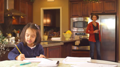 Cute little girl does her homework with help from her mother Stock Footage