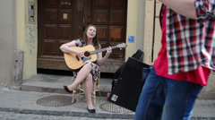 Young honest vocalist woman sing play guitar in oldtown street Stock Footage