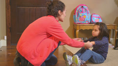 A little girl gets help from her mother getting her shoes for school Arkistovideo