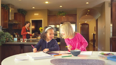 Two little girls sit at the table drawing when one tells the other a secret Stock Footage