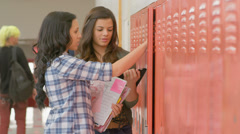 Stock Video Footage of Students stand at their locker and talk about other students behind their backs