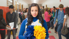 A high school girl in her cheerleader uniform stands in front of the camera Stock Footage