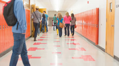 A busy school hallway with students walking to and from class - stock footage