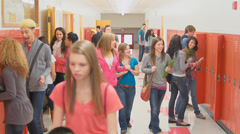 A busy hallway in a school full of students and a teacher going about their day Stock Footage