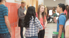 A school hallway is full of students standing in groups talking before class Stock Footage