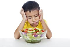 Lazy child to eat salad Stock Photos