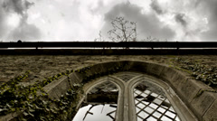 Broken arch church window with clouds timelapse pan Stock Footage
