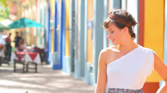 Spanish woman smiling and acting shy while on a colorful street Stock Footage