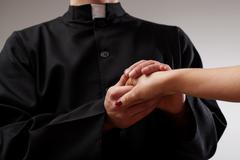 Priest holding believer hand Stock Photos