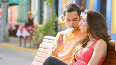 A young couple sits on a park bench and share an ice cream Stock Footage