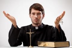young reverend with rosary and the bible - stock photo