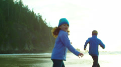 Two children in boots and sweaters walk towards the water while at the beach Stock Footage
