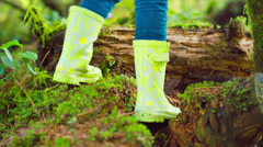 Little girls rain boots in a forest as she continues walking Stock Footage